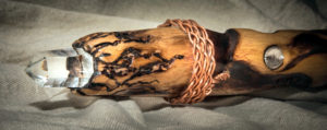 A one foot tall, three-inch diameter section of an oak staff, burned with artistic representations of flames. The left side of the image is the top of the staff showing a clear quartz crystal embedded in the top. 3 inches down from the top, copper wire is braided around the staff. 3 inches below the braided copper is an inset Herkimer diamond.